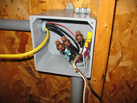The junction box where the power and signal wires join the conduit heading to the back wall of the shed.